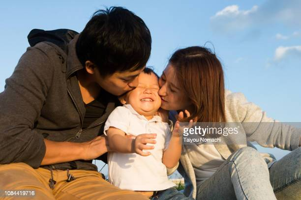a son who is happy to be kissed by his father and mother - forever young stock pictures, royalty-free photos & images