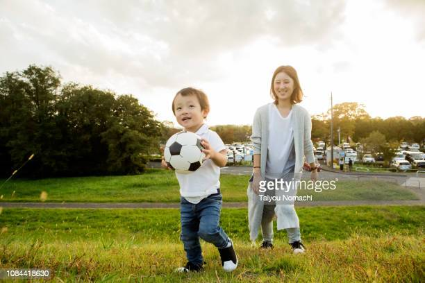son who plays with soccer ball, mother watching over. - football bulge stock photos and pictures