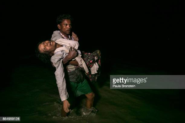 Sona Banu gets carried by Nobi Hossain to the shore of the Naf river as hundreds of Rohingya arrive by boats in the safety of darkness September 27...