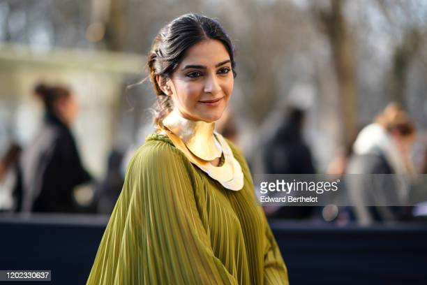 Sonam Kapoor wears a metallic golden large necklace a green pleated dress outside Elie Saab during Paris Fashion Week Haute Couture Spring/Summer...