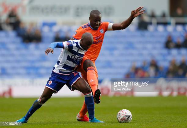 Sone Aluko of Reading FC and Sol Bamba of Cardiff City challenge for the ball during the FA Cup Fourth Round match between Reading FC and Cardiff...