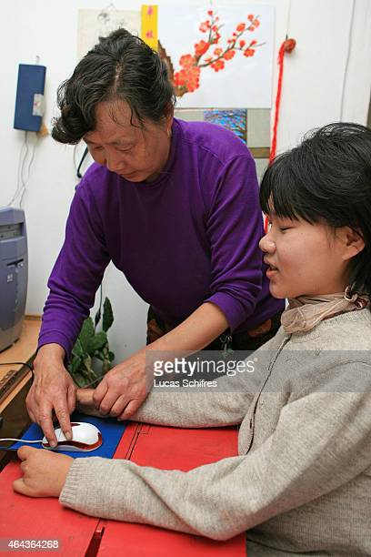 Song Fengying Li Yan's mother helps Li Yan to put her hands around the mouse to operate her computer in their home on May 7 2007 in Yinchuan Ningxia...