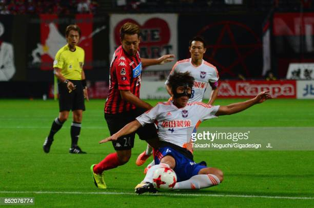 Song Ju Hun of Albirex Niigata and Akito Fukumori of Consadole Sapporo compete for the ball during the JLeague J1 match between Consadole Sapporo and...