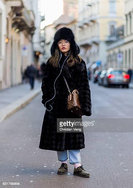 Song Yuxi is wearing a checked coat, fur hat, Louis Vuitton bag during Milan Men's Fashion Week Fall/Winter 2017/18 on January 15, 2017 in Milan,...