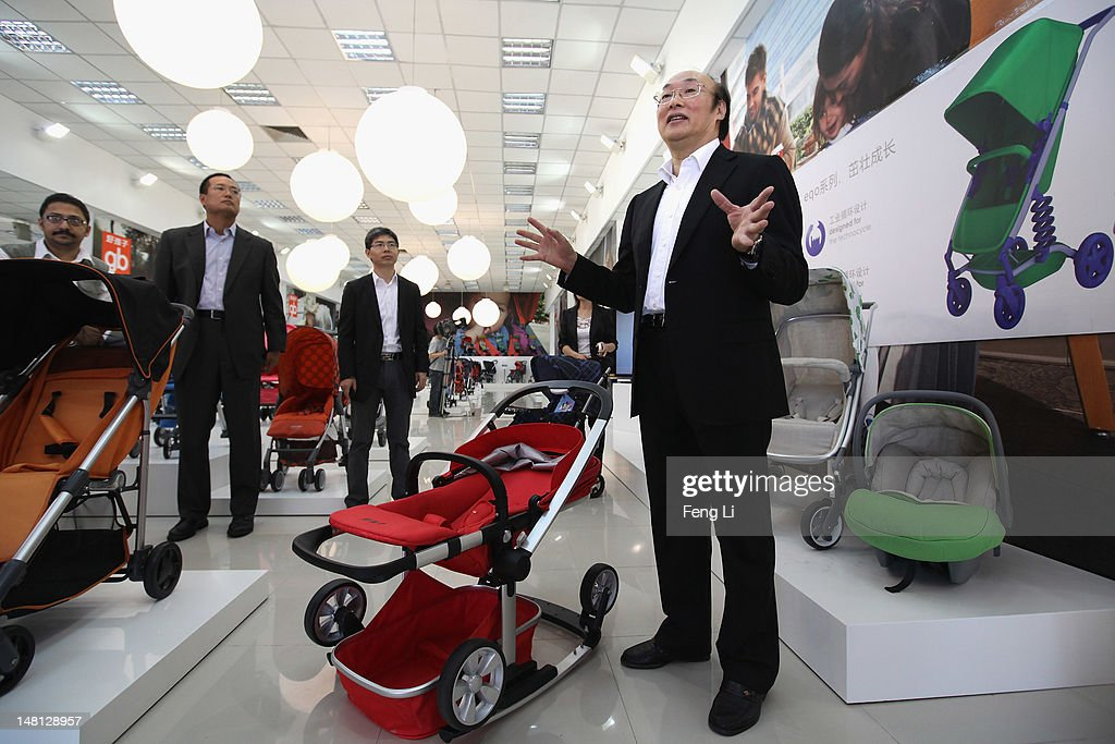 Song Zhenghuan (Right), the President of Goodbaby Group introduces the stroller to guests in the exhibition hall of Goodbaby Group Co., Ltd. on July 6, 2012 in Kunshan of Jiangsu Province, China. Chinese Premier Wen Jiabao said Tuesday that stabilizing economic growth is the most pressing matter currently facing China. China's central bank's sudden cut in the benchmark interest rates for the second time in a month confirmed the pessimistic view of the current economic situation.