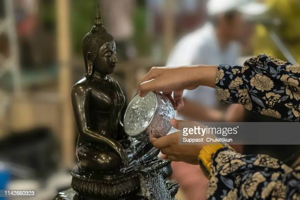 songkran festival in thailand,hand women use the water pouring to golden buddha - buddhist new year stock pictures, royalty-free photos & images