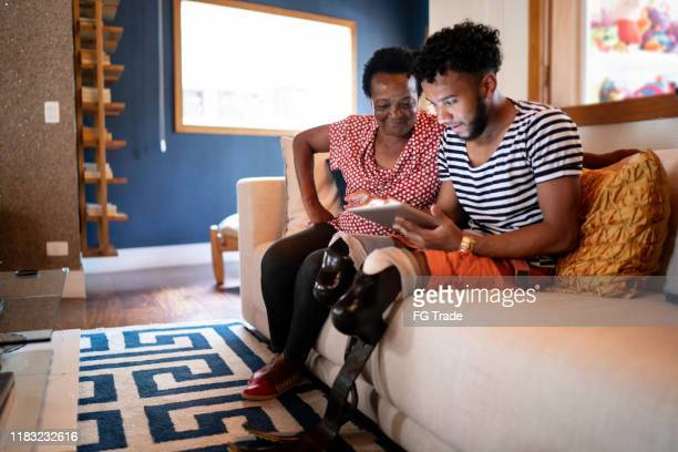 son/grandson using digital tablet with his mother/grandmother - amputee woman stock pictures, royalty-free photos & images