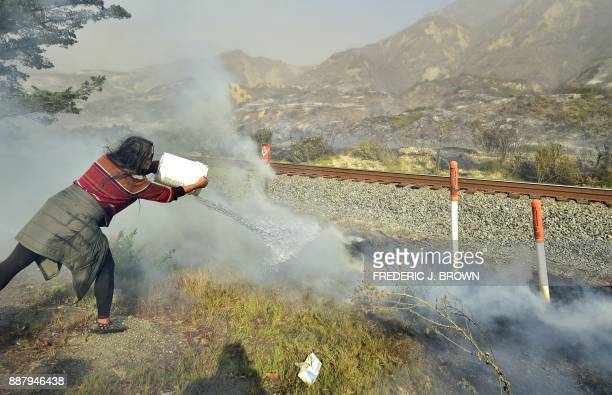 Songsri Kesonchampa tosses a bucket of water onto burning embers across the road from her home beside the US 101 freeway southbound in the beachside...