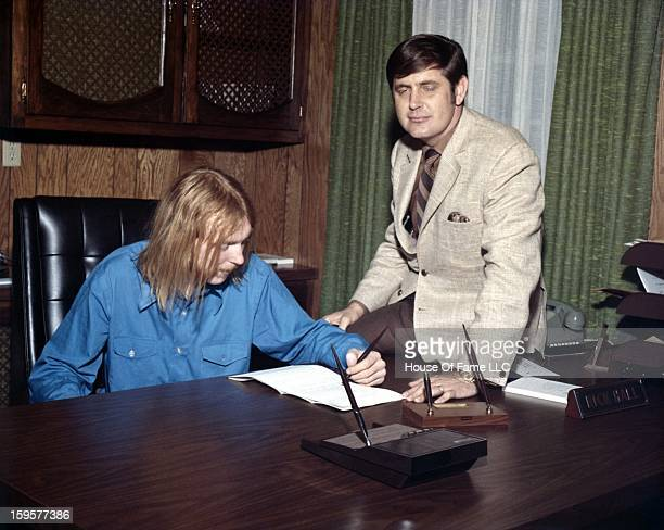 Songwriter and producer Rick Hall signs session guitarist Duane Allman to a contract in his office at FAME Studios in 1968 in Muscle Shoals Alabama