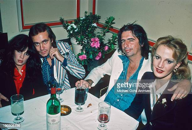 Songwriter Bernie Taupin and singer Alice Cooper with his wife Sheryl Cooper at a party for British rock group Queen March 1977