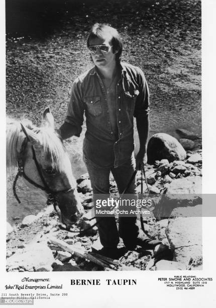 Songwriter Bernie Taupin poses for a portrait with a horse in November 1974