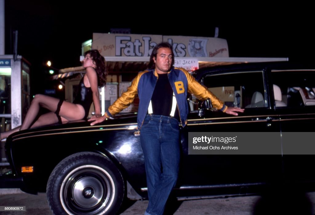 Songwriter Bernie Taupin poses for a portrait with a Rolls Royce car and his wife Toni Lynn Russo outside of Fat Jack's fast food shop on Ventura Blvd in Los Angeles, California in circa 1979.