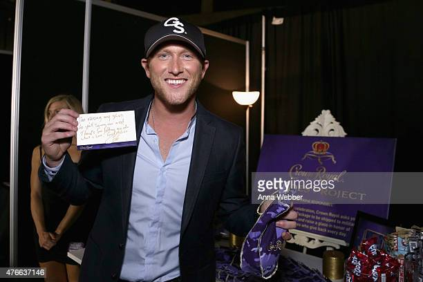 Songwriter Cole Swindell stuffs a Crown Royal CAMO care package to be sent to troops overseas backstage at the 2015 CMT Awards at Bridgestone Arena...