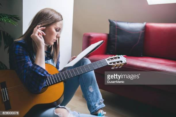 compositor se divertindo desfrutar passatempo conceito e escrita em papel de nota com a guitarra acústica perto por. instrumento musical de aprendizagem. - compositor - fotografias e filmes do acervo