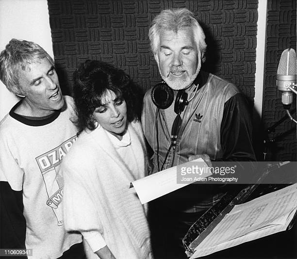 Songwriters Burt Bacharach Carole Bayer Sager and Kenny Rogers work together in a recording studio as they record music for the upcoming Disney...