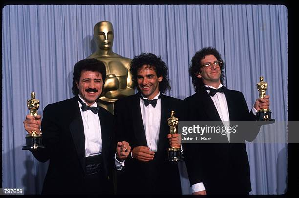 Songwriters Franke Previte John DeNicola and Donald Markowitz hold their Best Song Oscars for 'Dirty Dancing' at the Academy Awards April 11 1988 in...