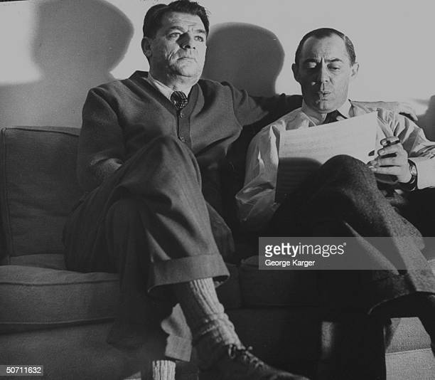 Songwriting partners Oscar Hammerstein and Richard Rodgers sitting on sofa while working on a song