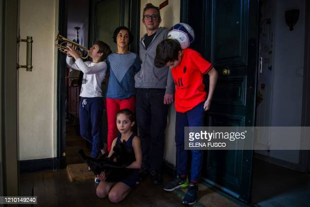 Sonia and her husband Marco pose with their children Celestin, Auguste and Lazarine by the entrance of their apartment, in Paris on April 10 on the...