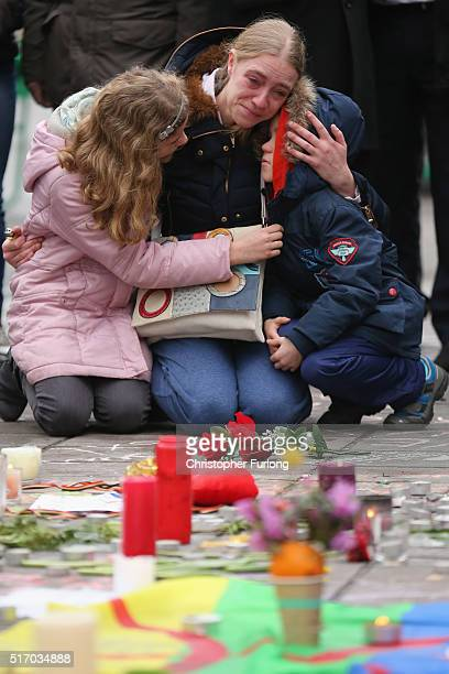 Sonia embraces her children Mateo and Alessia at The Place de la Bourse as she pays her respects to victims following yesterday's terrorists attacks...
