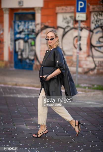 Sonia Lyson is seen wearing beige Massimo Dutti pants, Zara sandals, Uterque leather cape, &other strories white tshirt, Maria Black Creolen, Urban...