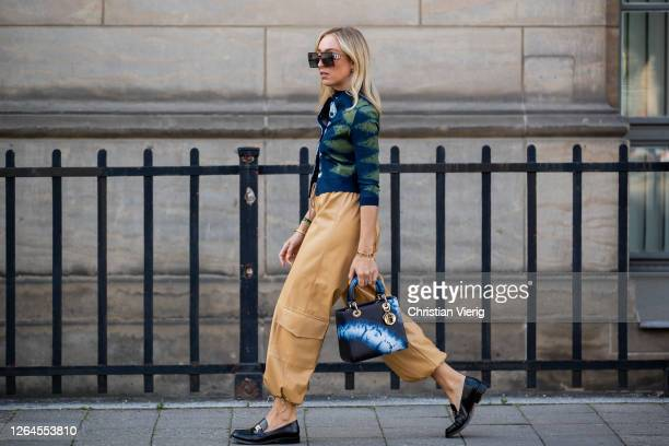 Sonia Lyson is seen wearing beige pants The Frankie shop cardigan Dior Dior bag loafers Dior sunglasses Dior August 07 2020 in Berlin Germany