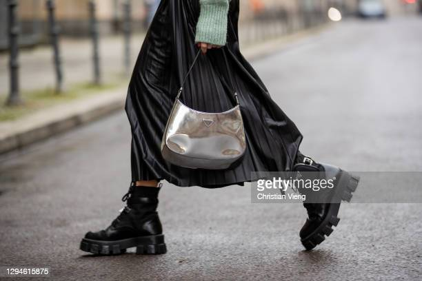 Sonia Lyson is seen wearing black boots Prada, silver bag Prada, green turtleneck knit and black pleated skirt Zara on January 05, 2021 in Berlin,...