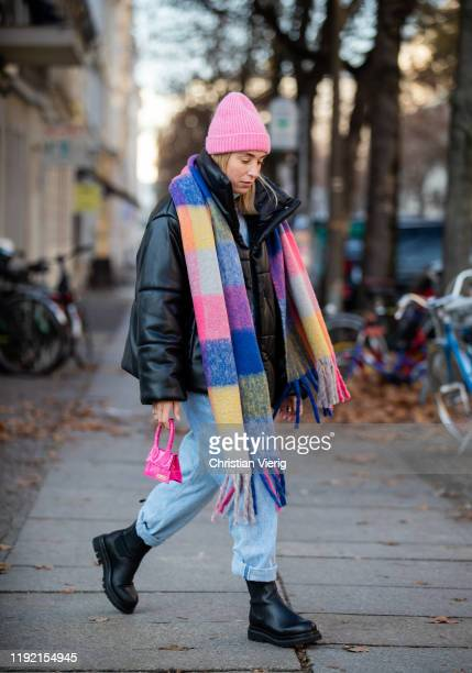 Sonia Lyson is seen wearing black Ducie boots, light blue AGOLDE denim jeans, black Nanushka vegan leather jacket, multi colored scarf with fringes...