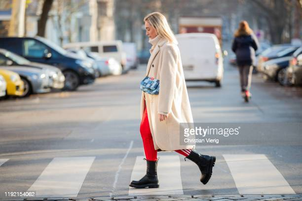 Sonia Lyson is seen wearing black Ducie boots, red Adidas jogger pants, beige Zara turtleneck and wool coat, blue Louis Vuitton bag on December 05,...