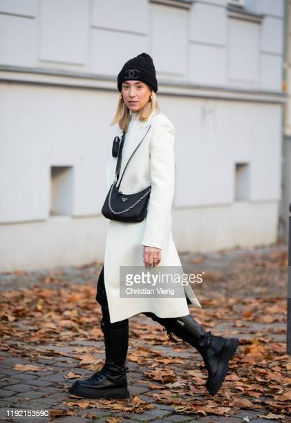 Sonia Lyson is seen wearing black laced boots Zara black pants and white wool coat Lala Berlin Prada bag Chanel beanie other Stories jumper on...