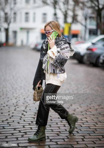 Sonia Lyson is seen wearing black leather pants and two tone sweater Topshop, Dior bag, poncho Dior, Oaykley sunglasses, olive Dior boots, Iphone...
