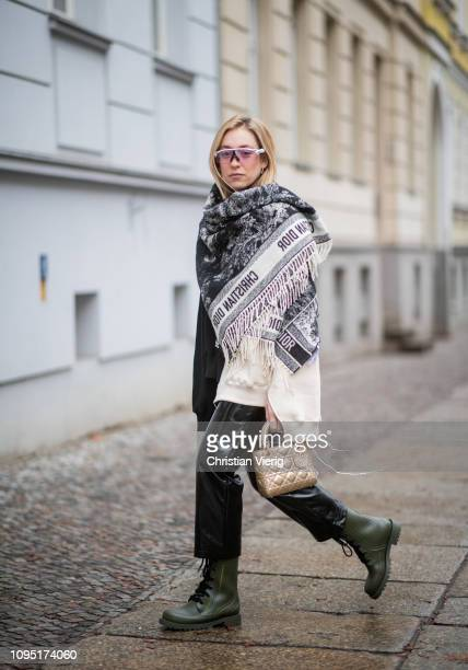 Sonia Lyson is seen wearing black leather pants and two tone sweater Topshop, Dior bag, poncho Dior, Oaykley sunglasses, olive Dior boots during the...