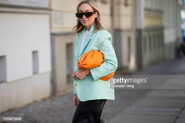 Sonia Lyson is seen wearing black pants and white tshirt The Frankie Shop mint blazer other stories orange Pouch bag Bottega Veneta Linda Farrow...
