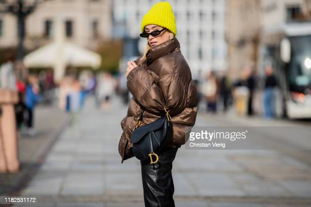 Sonia Lyson is seen wearing black pants, brown down feather jacket and yellow beanie Edited, Linda Farrow sunglasses, black Dior saddle bag on...
