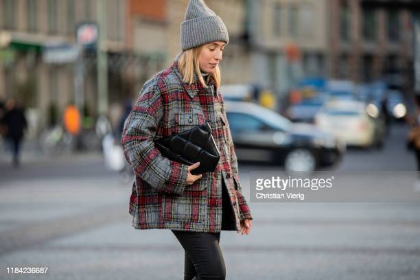 Sonia Lyson is seen wearing black pants Zara, cashmere turtleneck, Bottega Veneta bag, grey red plaid jacket Lala Berlin, grey beanie Acne on October...