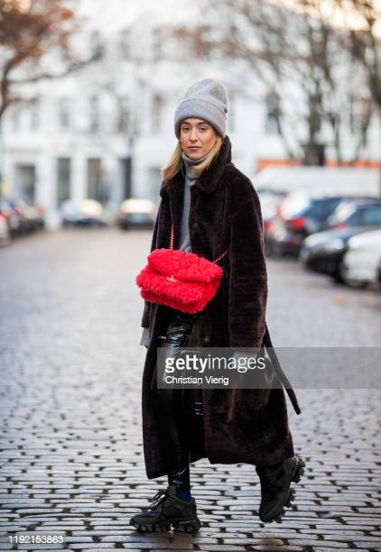 Sonia Lyson is seen wearing black Prada shoes, Worst Behavior varnish pants, red Chanel bag, brown Edited coat, grey Falke turtleneck Zara beanie on...