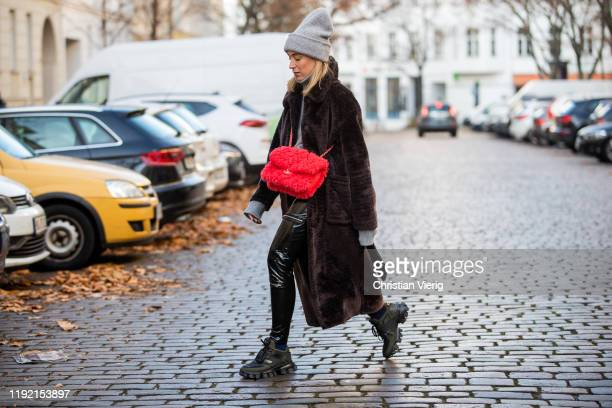 Sonia Lyson is seen wearing black Prada shoes Worst Behavior varnish pants red Chanel bag brown Edited coat grey Falke turtleneck Zara beanie on...