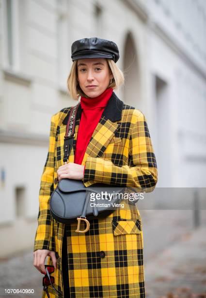 Sonia Lyson is seen wearing black Zara leather boots yellow black plaid Topshop wool coat red cashmere turtleneck Zara black leather cap Zara...
