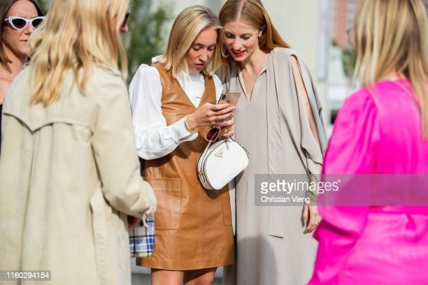 Sonia Lyson is seen wearing brown dress white Prada bag and Lisa Banholzer wearing beige dress with slit while looking on the phone outside William...