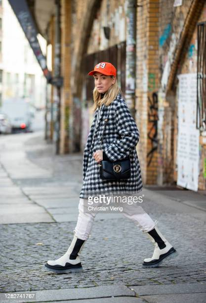 Sonia Lyson is seen wearing creme white black two tone boots Bottega Veneta BV TIRE, jogger pants Edited, checkered black white coat and orange cap...