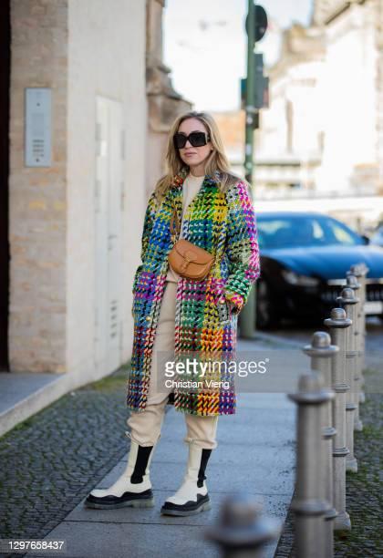 Sonia Lyson is seen wearing creme white black two tone boots Bottega Veneta, Pangaia jogger suit, pants and top, multi colored coat Escada,...