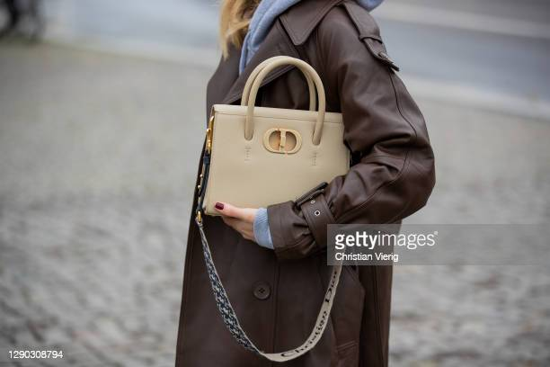 Sonia Lyson is seen wearing Dior bag in beige, brown trench coat Ducie, Sundarbay hoody in grey, black flared pants with slit on December 09, 2020 in...