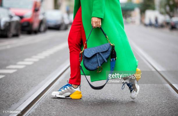 Sonia Lyson is seen wearing Dior sneakers red jogging pants Adidas green wool coat Topshop denim saddle bag and strap Dior on September 03 2019 in...