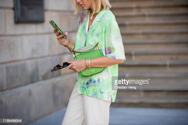 Sonia Lyson is seen wearing green bag Prada, white Monki pants, Wald Berlin jewellery, Edited sandals, Alexandre Vauthier sunglasses, green button...
