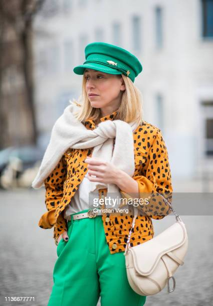 Sonia Lyson is seen wearing green pants hat jacket with animal print Fabienne Chapot and Dior saddle bag on March 18 2019 in Berlin Germany