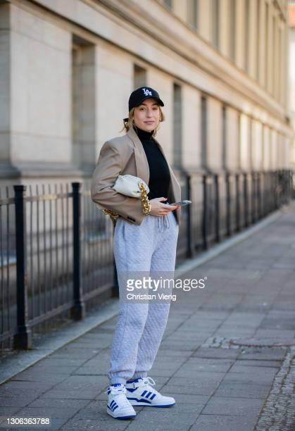 Sonia Lyson is seen wearing grey jogger pants Topshop, sneaker Forum 84 Adidas, beige cropped blazer Zara, black turtleneck, New Era cap, Bottega...