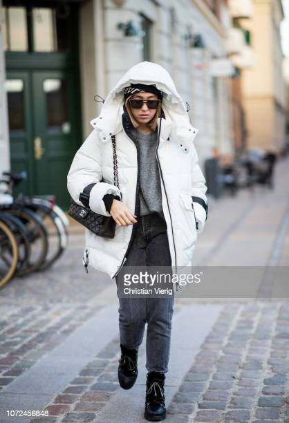 Sonia Lyson is seen wearing Jimmy Choo boots black Levis jeans Zara knit white Zara oversized down feather parka Chanel bag Balenciaga beanie Dior...