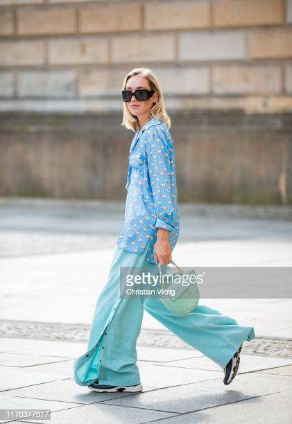 Sonia Lyson is seen wearing multi colored Chanel sneaker turquois Uterque pants with buttons on the side blue button shirt with elephant print Zara...