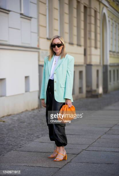 Sonia Lyson is seen wearing orange high heels By Far x Luisa via Roma black pants and white tshirt The Frankie Shop mint blazer other stories orange...
