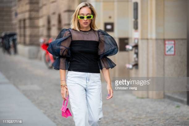 Sonia Lyson is seen wearing pink mini bag Jacquemus, white jeans Sandro, black sheer ruffled top Zara, neon sunglasses Gucci on August 26, 2019 in...