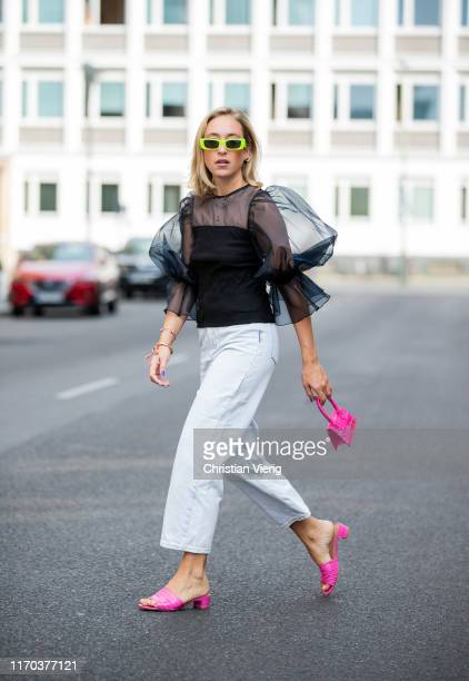 Sonia Lyson is seen wearing pink sandals Topshop pink mini bag Jacquemus white jeans Sandro black sheer ruffled top Zara neon sunglasses Gucci on...